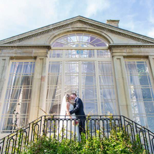Bride & Groom standing on the stairs kissing in front of the tall windows at Ickworth Hotel