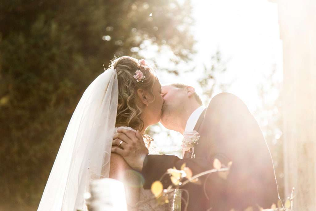 Bride & Groom kissing with trees in the background and sun shining through