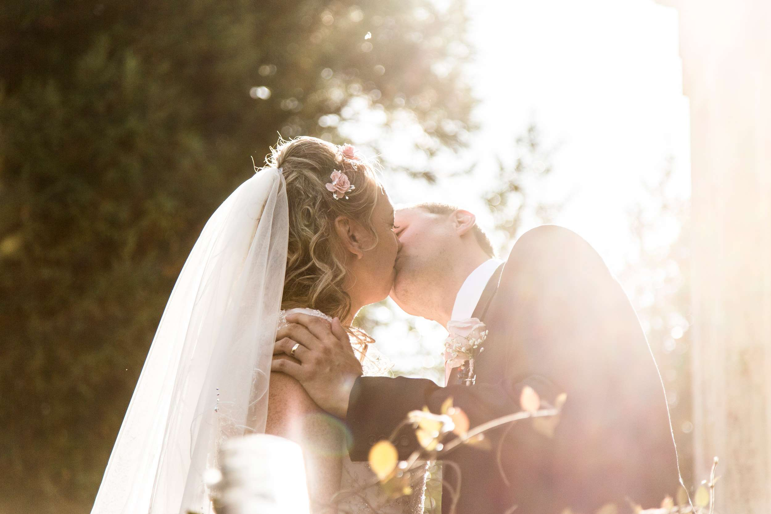 Norfolk Wedding Photography. Bride & Groom kissing with trees in the background and sun shining through