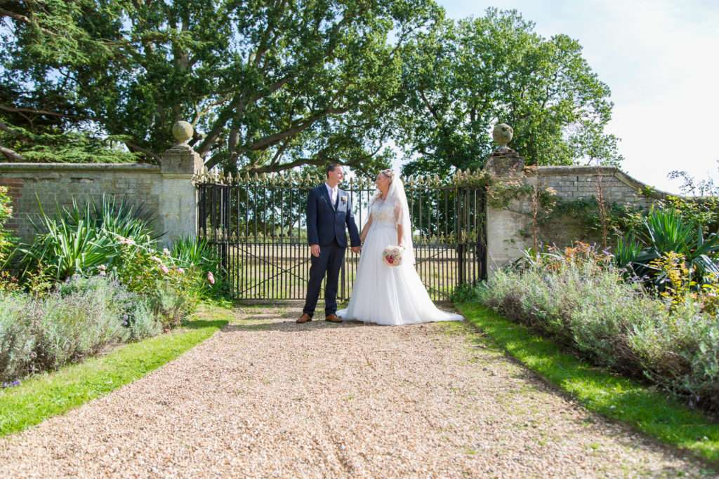 Bride & Groom holding hands in front of a gate on a shingle pathway at Ickworth Hotel in Suffolk
