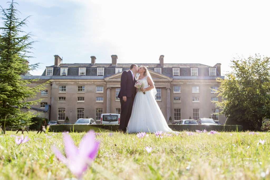 Bride & Groom kissing in front of The Ickworth Hotel in Suffolk