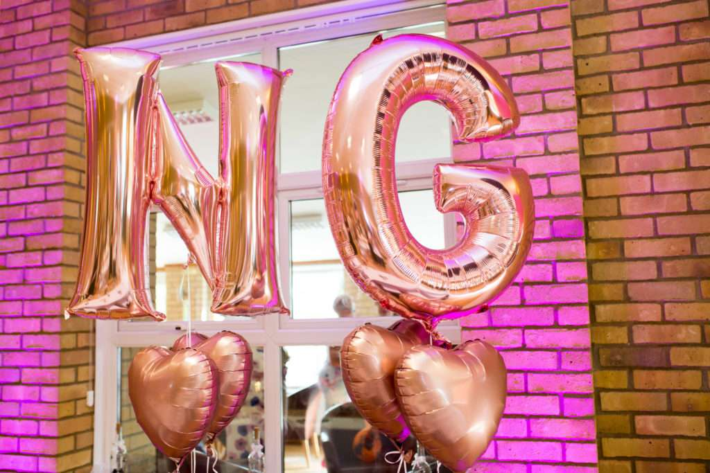 N & G letters helium balloons in rose gold and hearts at a wedding