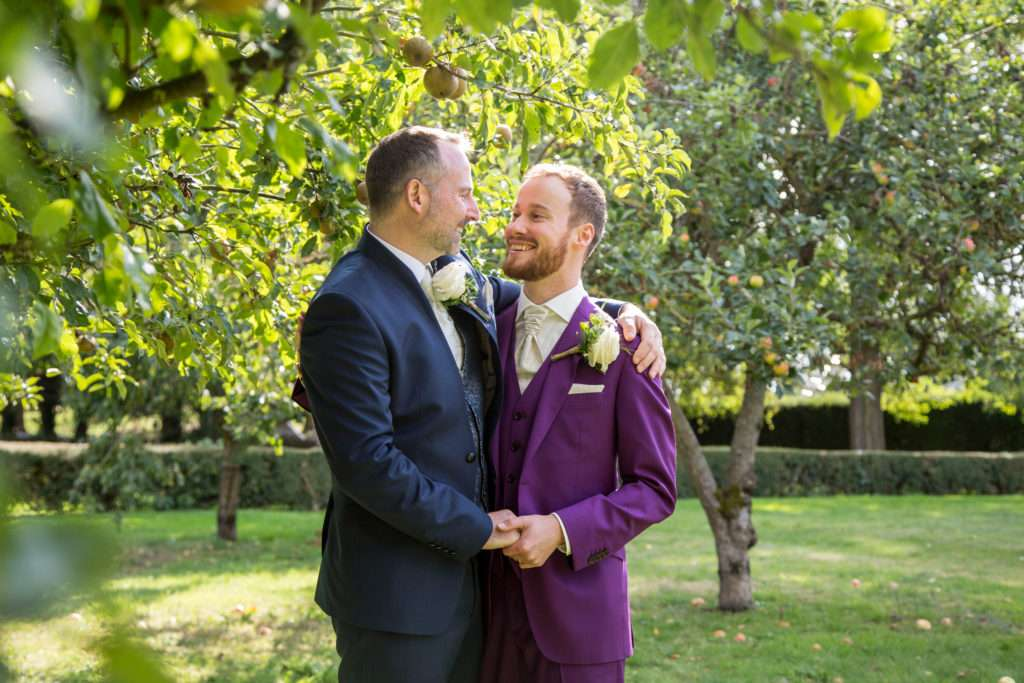 Two Grooms arm in arm on their wedding day in the gardens at Hockwold Hall in Norfolk