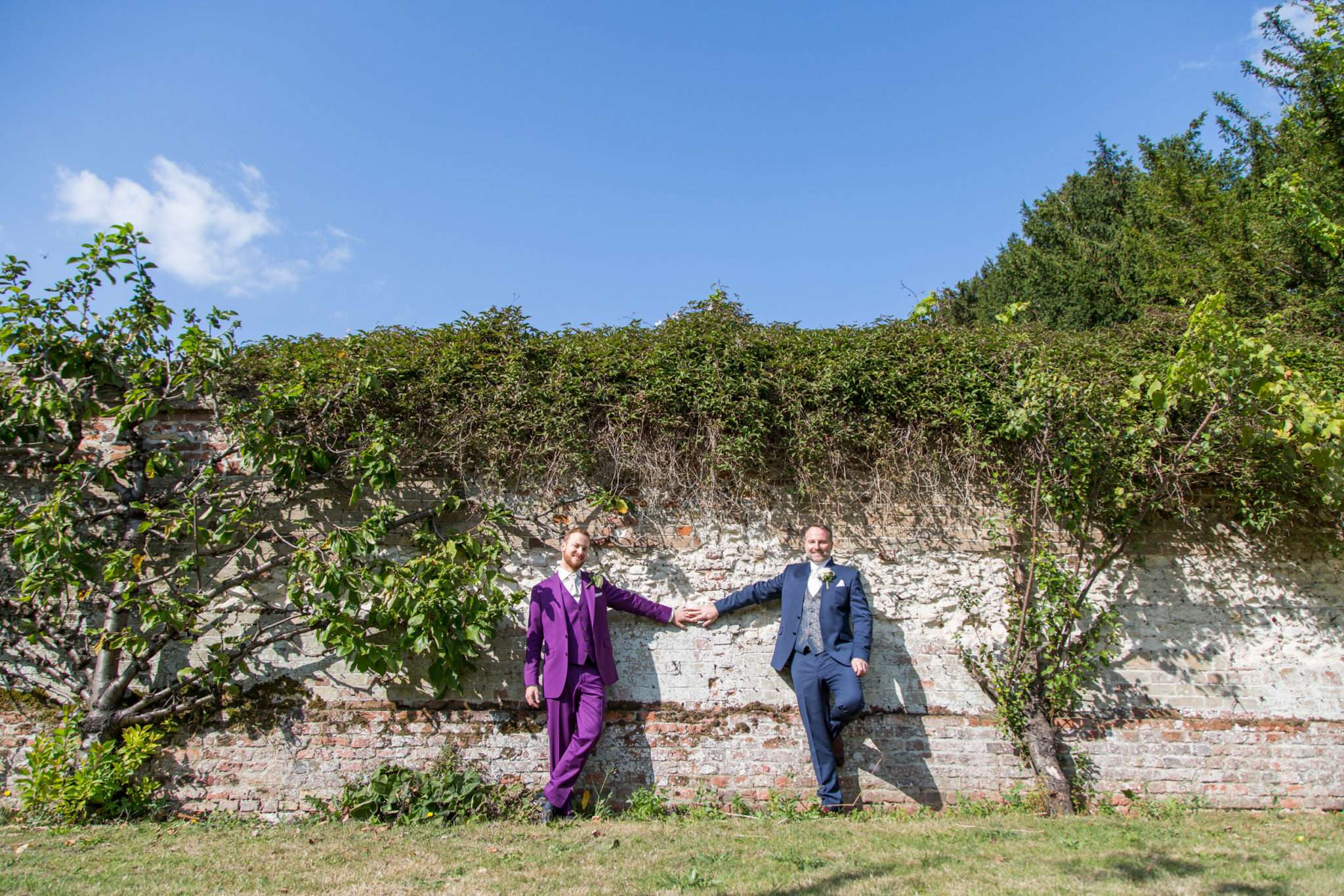 Two Grooms with arms stretched out standing in front of a flint wall at Hockwold Hall in Norfolk