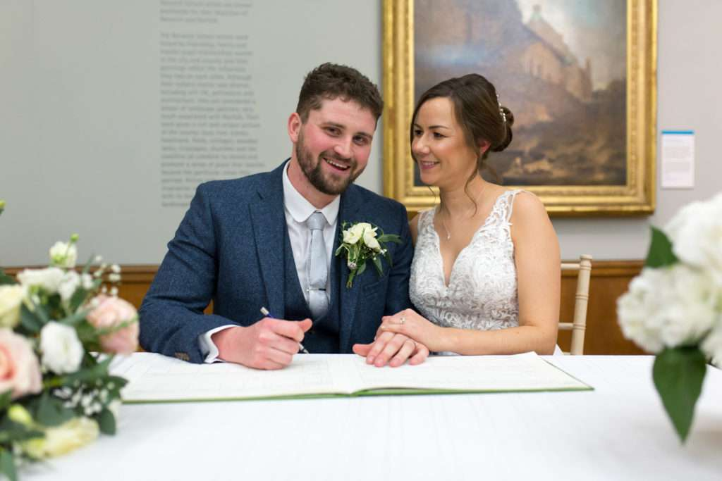 Bride & Groom sat at Norwich Castle signing the register