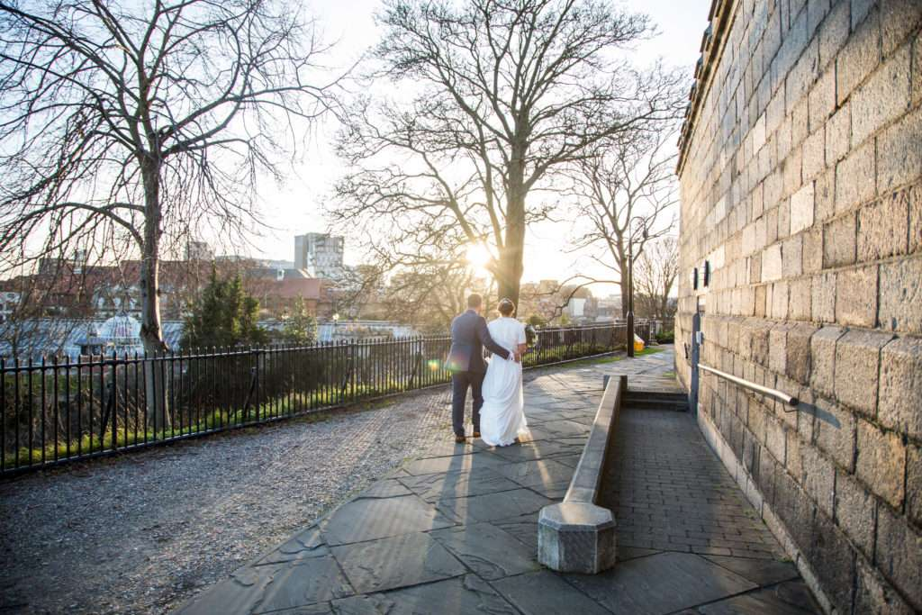Bride & Groom arm in arm walking away from Norwich Castle