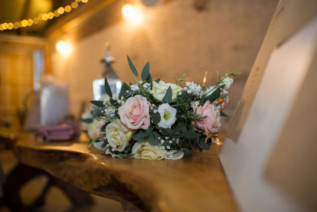Bridal bouquet laid on a wooden table at Glebe Farm Barn