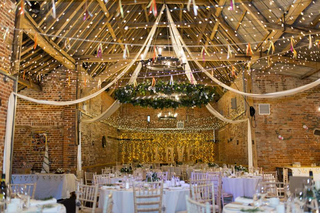 Glebe Farm Barn in Norwich set for a wedding with tables, chairs and linen with drapes and fairy lights