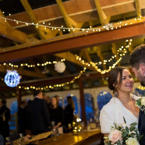 Bride & Groom arm in arm at Glebe Farm Barn with twinkling fairy lights in the background
