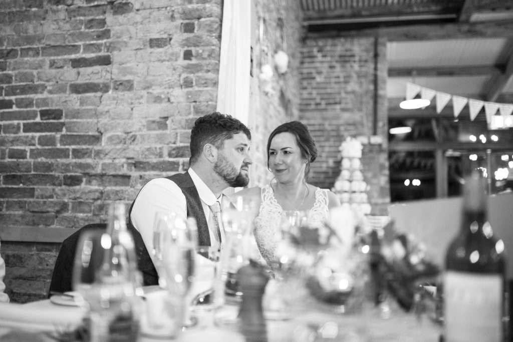 Bride & Groom sat at the table listening to speeches at Glebe Farm Barn wedding