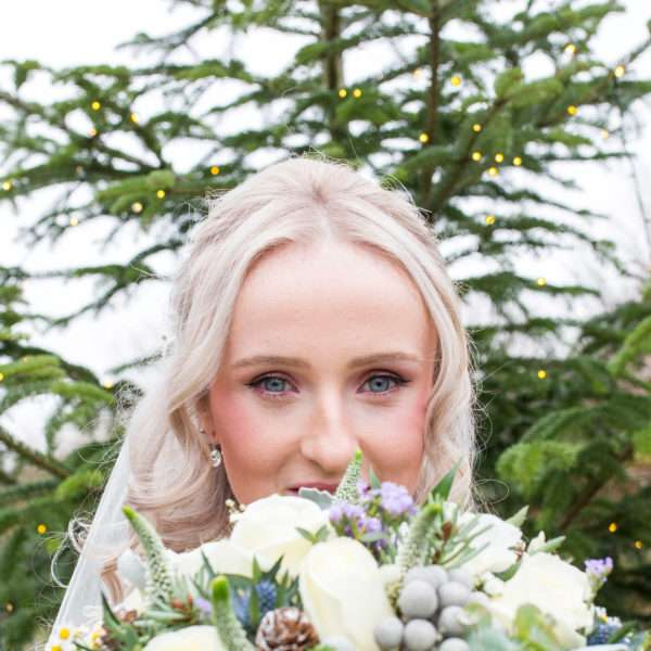 Bride peeking over her bouquet with a christmas tree with sparkling lights behind her