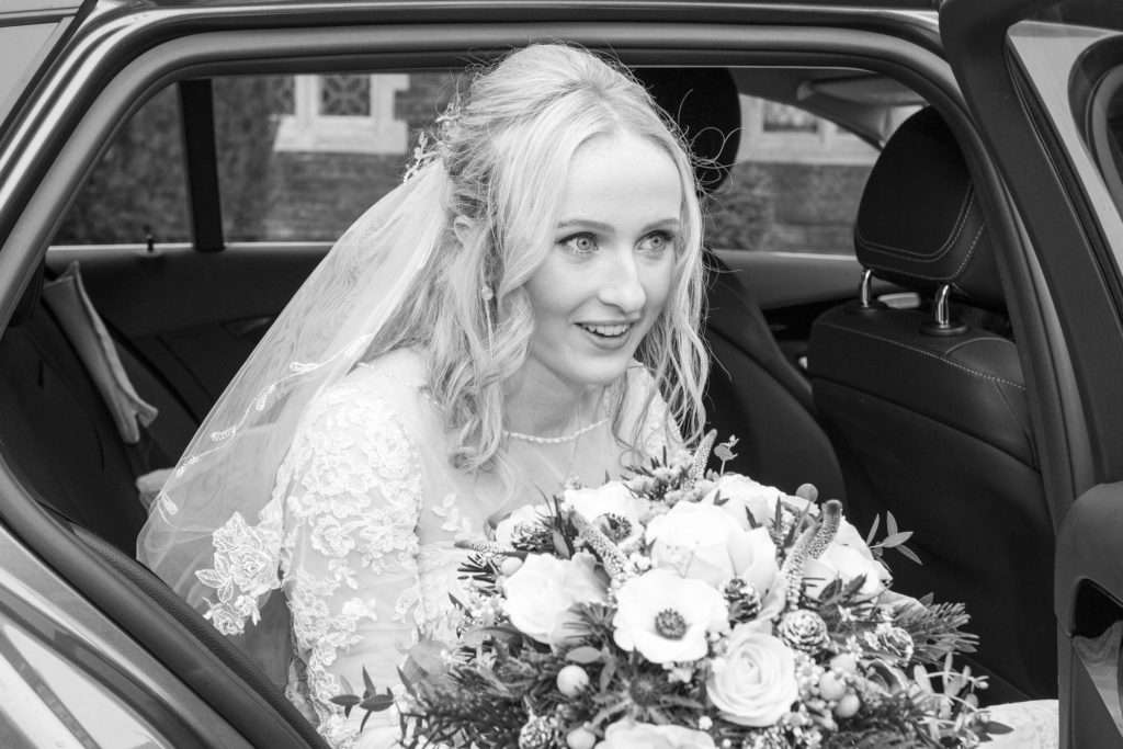 Bride with her bouquet getting out of a Mercedes wedding car