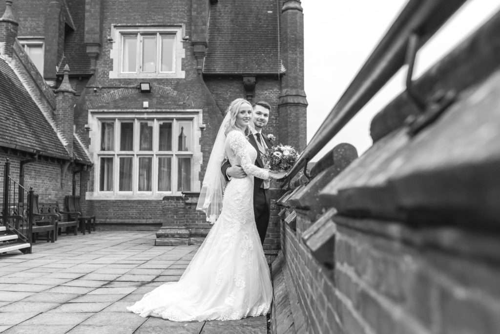 Bride & Groom standing on the balcony at Dunston Hall Hotel