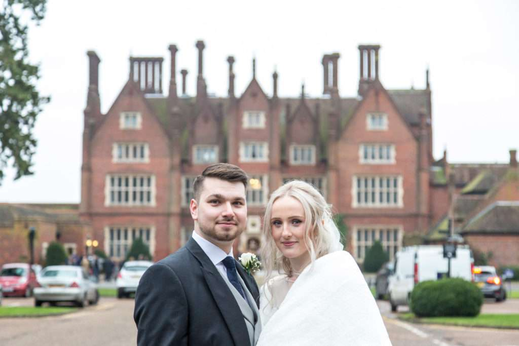 Bride & Groom standing infront of Dunston Hall Hotel in Norfolk