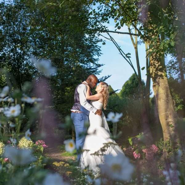 Bride & Groom kissing in the trees at Chaucer Barn - Norfolk Wedding Photographer