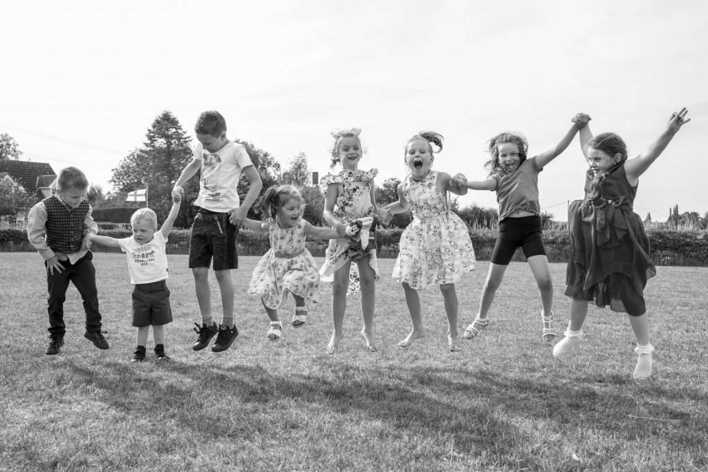 Children holding hands jumping in the air at a wedding