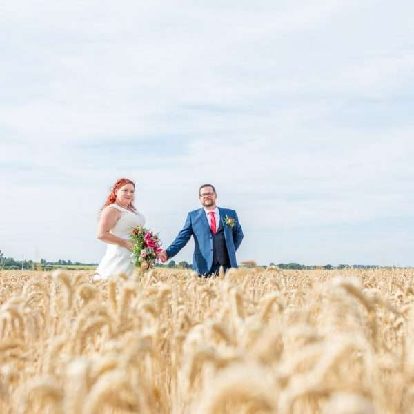 Bride & Groom holding hands in a field of wheat