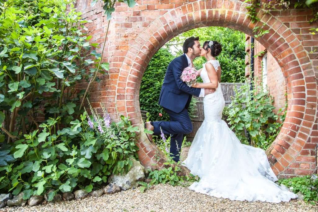 Bride & Groom kissing surrounded by brick wall at Norfolk Mead Hotel