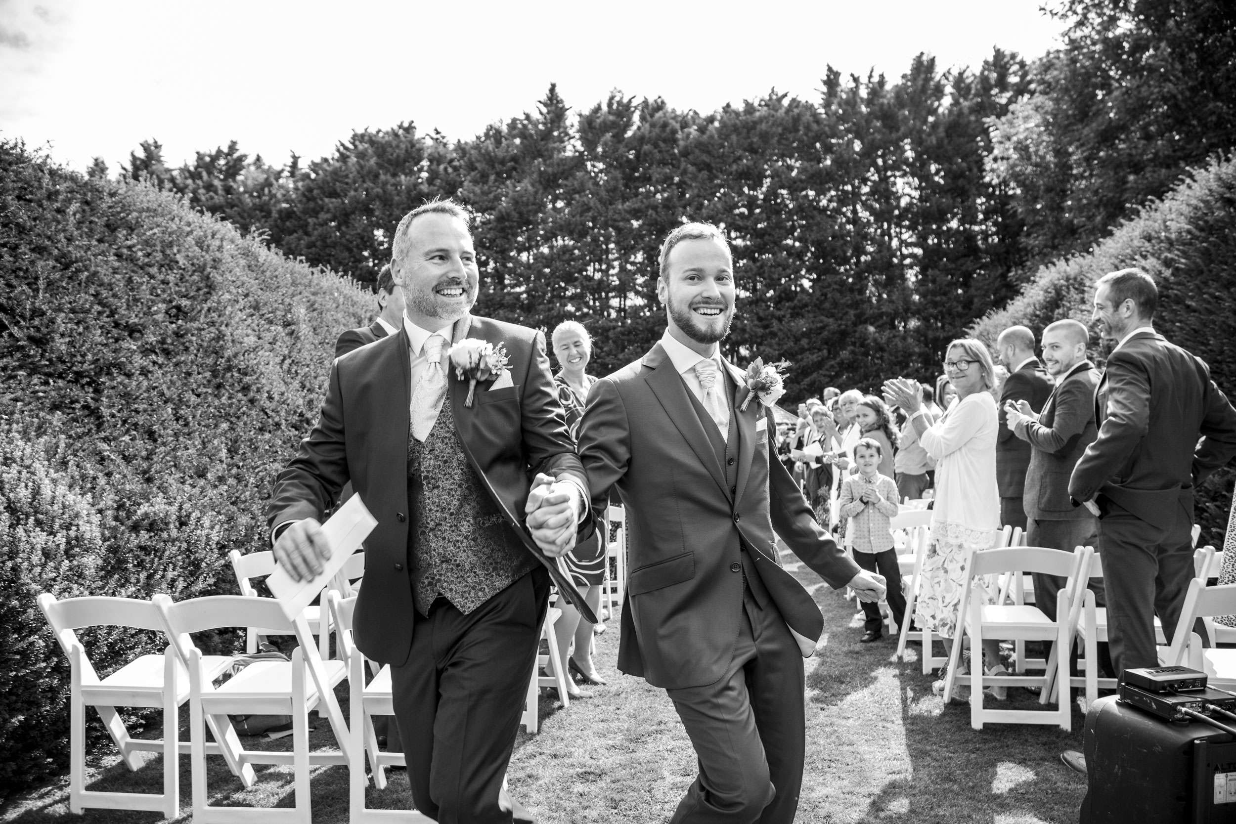 Grooms dancing down the aisle at their wedding at Hockwold Hall in Norfolk