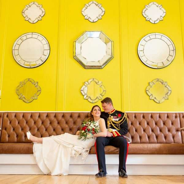 Bride laying on the sofa next to her groom at The Assembly House in Norwich. Bright yellow walls decorated with mirrors.
